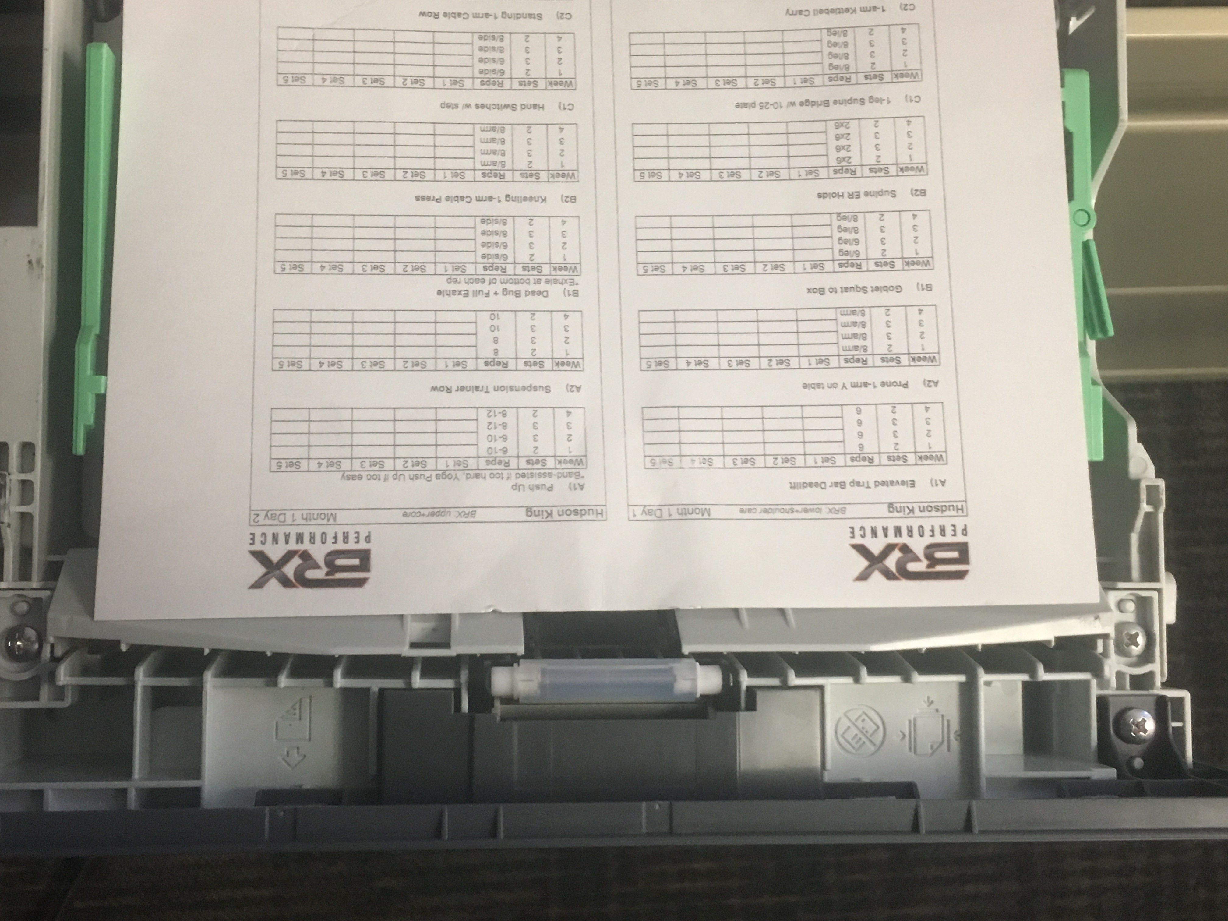Once the program's day 1&2 side is printed, review for any possible errors. If any errors or questions arise notify the staff member assigned to writing that athlete's program. If there are no errors, print the next tab, which has days 3&4. Place back into printing tray as seen above (logos nearest you).