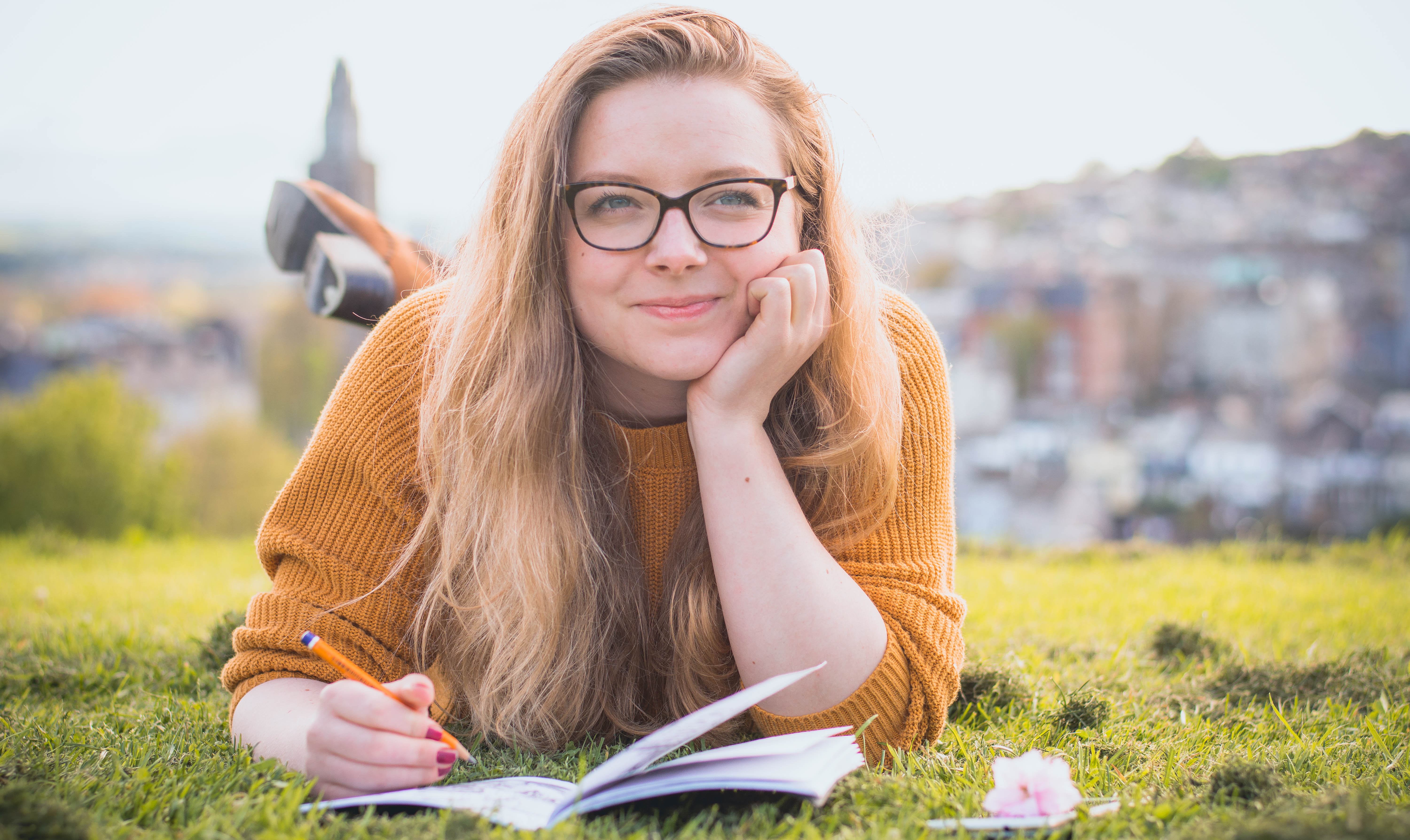 https://www.pexels.com/photo/woman-lying-on-green-grass-while-holding-pencil-1458318/